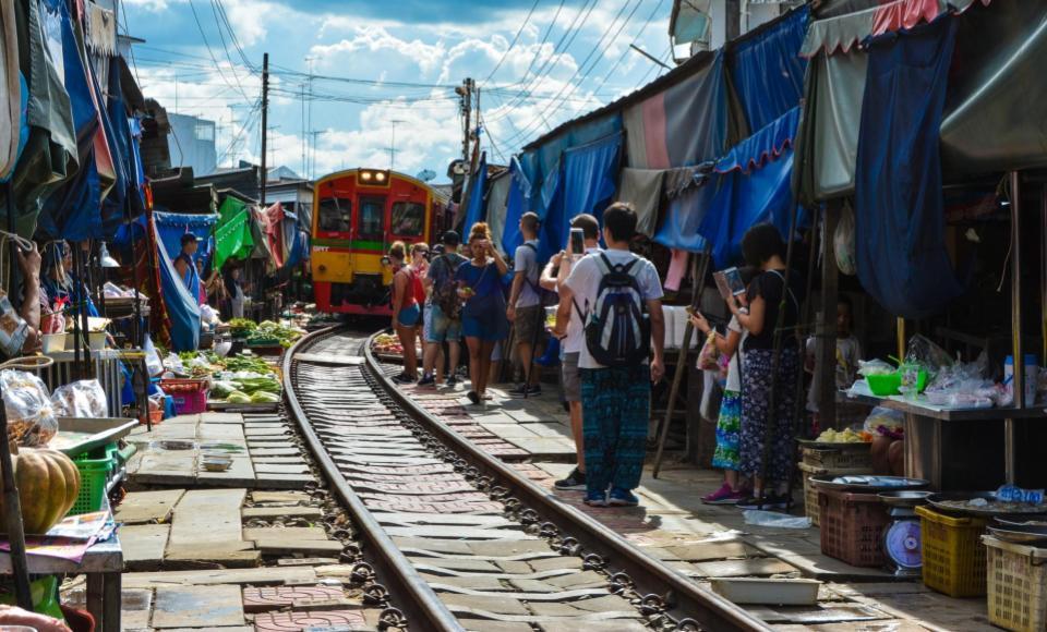 Tren pasando por el mercado con turistas haciendo fotos